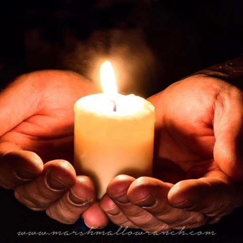 A candle held in hands.