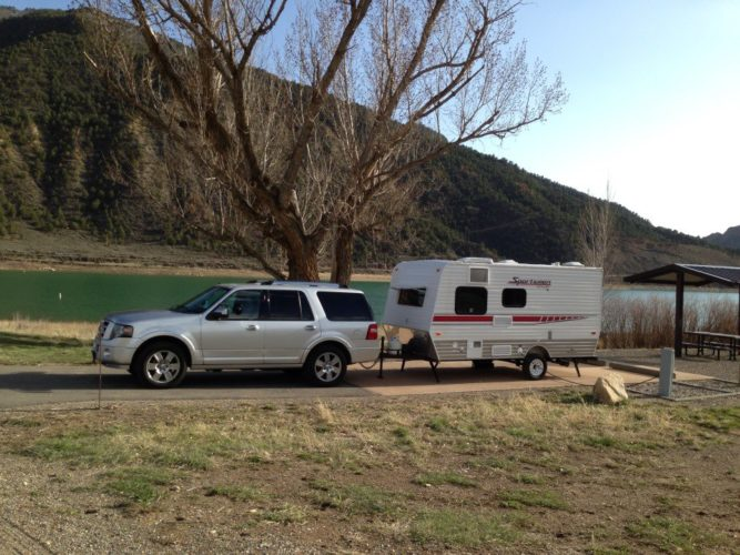 Ford Expedition and Sportsmen Classic travel trailer by a lake in Rifle Falls State Park, Colorado.