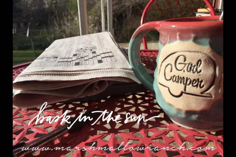 Girl Camper mug and crossword on the porch